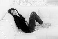 Młoda kobieta czuje silnego miesiączka bólu obsiadanie na kanapie czarny i biały w domu fotografia stock