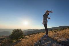 Młoda kobieta czuje swobodnie na pięknej górze przy zmierzchem zdjęcie royalty free