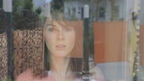 Młoda kobieta czyści okno i spojrzenia dokuczaliśmy przez okno zbiory wideo