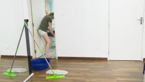 Młoda kobieta czyści sypialnię z czyści produktami wyposażeniem i, sprzątania pojęcie zdjęcie wideo
