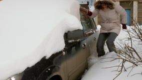 Młoda kobieta czysty samochód po śnieżnej burzy z cykliną zbiory