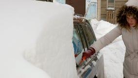 Młoda kobieta czysty samochód po śnieżnej burzy z cykliną zdjęcie wideo