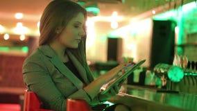 Młoda kobieta czyta cyfrową pastylkę zbiory wideo