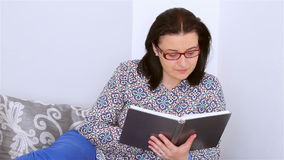 Młoda kobieta czyta książkę na leżance zbiory