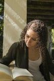 Młoda kobieta czyta książkę w jesieni Obrazy Royalty Free