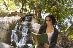 Młoda kobieta czyta książkę w jesieni Obraz Royalty Free