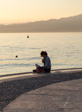 Młoda kobieta czyta książkę z zmierzchu widokiem na deptaku Jeziorny Garda w Lazise Fotografia Stock