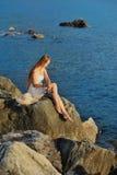 Młoda kobieta czyta książkę z zmierzchu widokiem przy morzem Fotografia Stock