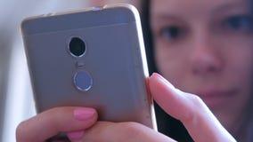Młoda kobieta czyta książkowych chodzeń oczy na smartphone interneta online wyszukuje stronach zbiory