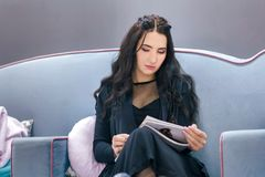 Młoda kobieta czyta magazyn podczas gdy czekający w fryzjerstwo salonie fotografia royalty free