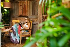 Młoda kobieta czyta papierową książkę na outside werandzie Zdjęcia Royalty Free