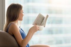 Młoda kobieta czyta papierową książkę w kawiarni z kawą obrazy stock