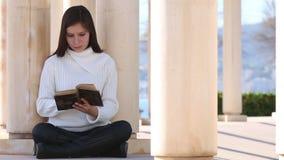 Młoda kobieta czyta starą książkę outside zdjęcie wideo
