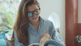 Młoda kobieta czytelniczy magazyn na kanapie w hotelu zbiory wideo