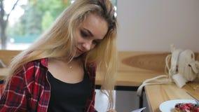 Młoda kobieta czytelniczy magazyn w kawiarni zdjęcie wideo