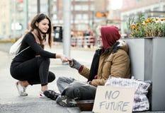Młoda kobieta daje pieniądze bezdomny żebraka mężczyzny obsiadanie w mieście zdjęcie royalty free