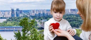 Młoda kobieta daje trykotowemu sercu mały dziecko obrazy royalty free