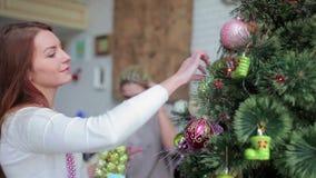 Młoda kobieta dekoruje choinki w domu zdjęcie wideo
