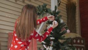 Młoda kobieta dekoruje choinki z czerwonymi piłkami w domu zbiory wideo