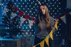 Młoda kobieta dekoruje izbowe flaga, girlandy przygotowywa dla świętowań bożych narodzeń zdjęcia royalty free