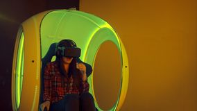 Młoda kobieta doświadcza rzeczywistości wirtualnej obsiadanie w interaktywnym chodzenia krześle Zdjęcie Stock