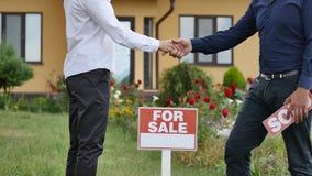 Młoda kobieta dostaje klucz jej nowy dom od ich pośrednika handlu nieruchomościami na drzwi nowego domu tło obrazy royalty free