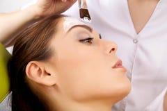 Młoda kobieta dostaje piękno skóry maski traktowanie na jej twarzy z Fotografia Stock