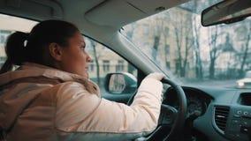 Młoda kobieta dzwoni na telefonie komórkowym podczas gdy jadący samochodową synkliny miasta ulicę zbiory