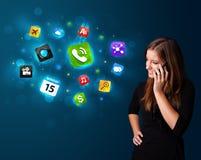 Młoda kobieta dzwoni telefonem z różnorodnymi ikonami Zdjęcie Royalty Free