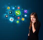 Młoda kobieta dzwoni telefonem z różnorodnymi ikonami Fotografia Stock