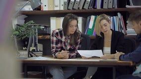 Młoda kobieta egzamininuje niektóre diagram, miie ten papier i rzuca, then zbiory wideo