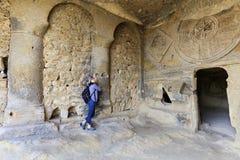 Młoda kobieta egzamininuje wnętrze starych podziemnych church's szpaltowa sala, rzeźbiącego w piaskowcową falezę zdjęcie stock