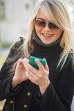 Młoda kobieta flirtuje wiadomościami Obraz Stock