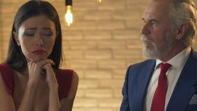 Młoda kobieta flirtuje z starym bogatym człowiekiem, pyta dla drogiej teraźniejszości, imitacji miłość zbiory
