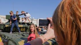 Młoda kobieta fotografująca na telefonie komórkowym blisko wielkiego zbiornika i dzieci siedzimy na dachu zielony pojazd wojskowy zbiory wideo