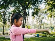 Młoda kobieta grże up jej ciało i robi joga w parku rozciągać jej ręki przygotowywać dla ćwiczyć zdjęcie royalty free
