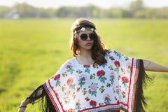 Młoda kobieta hipis w okularach przeciwsłonecznych stoi outdoors ręki szeroko rozpościerać Outdoors zdjęcia royalty free