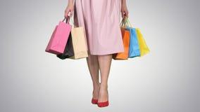 Młoda kobieta iść na piechotę niosący kolorowe torby na zakupy na gradientowym tle zbiory wideo