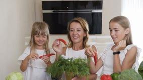 Młoda kobieta i dwa dziewczyny ubierających w biel ubraniach bawić się z chili pieprzem i zieleń koperem w kuchni w domu zbiory wideo