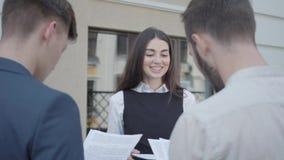 Młoda kobieta i dwa mężczyzny w formalnej odzieży dyskutuje dokumenty na tarasie Dziewczyna daje papierom koledzy zbiory