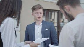 Młoda kobieta i dwa mężczyzny w formalnej odzieży dyskutuje dokumenty na tarasie Mężczyzna daje papierom koledzy zbiory wideo