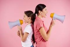 Młoda kobieta i dziewczyna krzyczy w megafonach fotografia stock