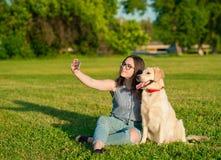 Młoda kobieta i jej życzliwy pies bierze selfie przy parkiem zdjęcie royalty free
