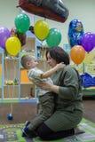 Młoda kobieta i jej mały syna obsiadanie na krześle na tle kolorowi balony fotografia royalty free