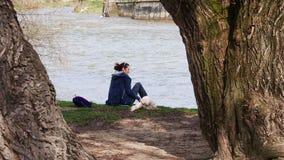 Młoda kobieta i jej pies relaksujemy przy rzeką Zdjęcia Royalty Free
