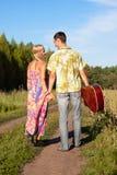 Młoda kobieta i mężczyzna z gitarą idziemy na drodze Obraz Stock