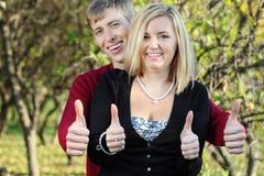 Młoda kobieta i mężczyzna za jej kciukiem up w parku i uśmiechem fotografia royalty free