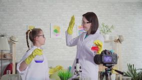 Młoda kobieta i nastoletniej dziewczyny blogger w chemii lab, szkoła projekta mieszanki odczynniki i dajemy pięć, spojrzenie w zbiory wideo