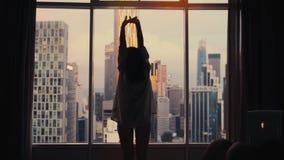 Młoda kobieta i przyglądający otwieramy zasłony na dużych nadokiennych rozciągliwość wzrostów rękach out jej mieszkanie na miasto zbiory wideo