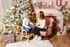 Młoda kobieta i siedmioletni dziecka spojrzenie przy each inny w Bożenarodzeniowym położeniu zdjęcia royalty free